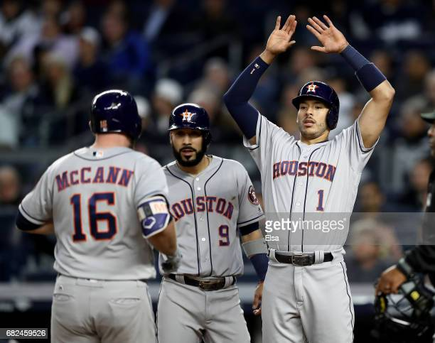 Marwin Gonzalez and Carlos Correa of the Houston Astros congratulate teammate Brian McCann after McCann drove them all home with a home run in the...