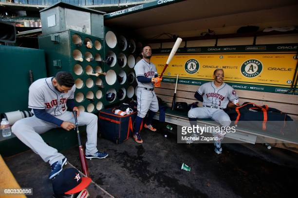 Marwin Gonzalez Jose Altuve and Carlos Correa of the Houston Astros relax in the dugout prior to the game against the Oakland Athletics at the...