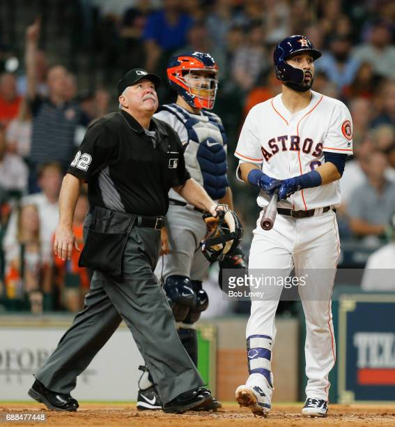 Marwin Gonzalez of the Houston Astros along with catcher Juan Centeno and home plate umpire Dana DeMuth watch as the ball leaves the park in the...