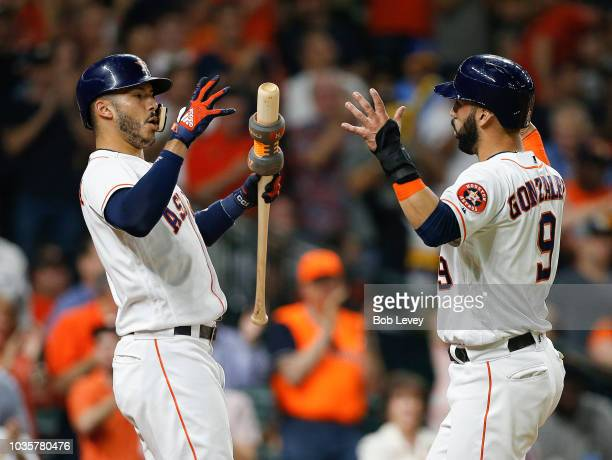 Marwin Gonzalez of the Houston Astros celebrates with Carlos Correa of the Houston Astros after an umpire review overturned the call on the field and...
