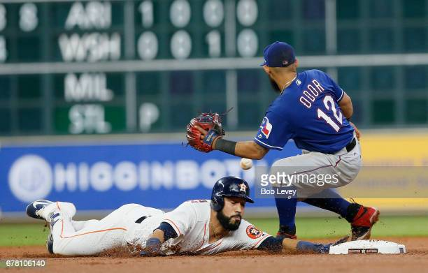 Marwin Gonzalez of the Houston Astros dives back into second base as Rougned Odor of the Texas Rangers can't handle the throw in the second inning at...