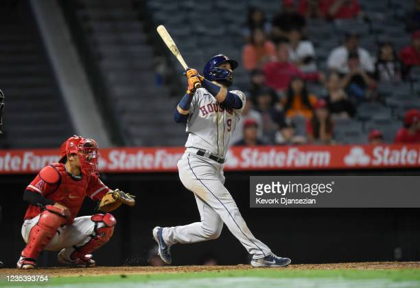 Marwin Gonzalez of the Houston Astros hits a grand slam home run with catcher Kurt Suzuki of the Los Angeles Angels looking on against relief pitcher...