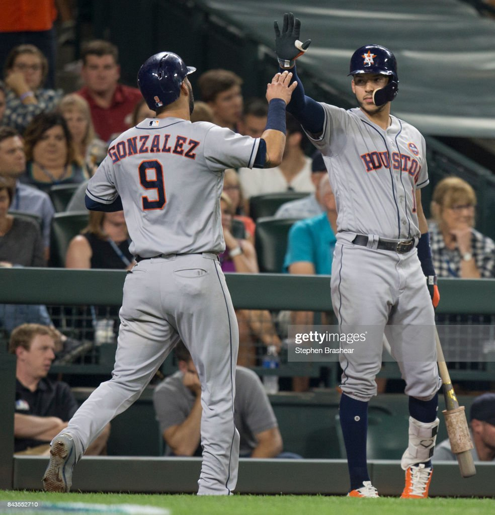 Marwin Gonzalez #9 of the Houston Astros is congratulated by Carlos Correa #1 of the Houston Astros after scoring a run on a hit by George Springer #4 of the Houston Astros off of relief pitcher Nick Vincent #50 of the Seattle Mariners during the seventh inning of a game at Safeco Field on September 6, 2017 in Seattle, Washington.