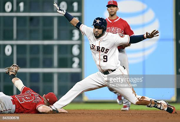 Marwin Gonzalez of the Houston Astros signals himself safe after hitting a double beating the tag of Johnny Giavotella of the Los Angeles Angels of...