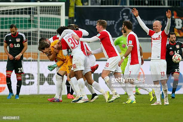 Marwin Hitz keeper of Augsburg celebrates scoring the 2nd team goal with his team mates whilst Oemer Toprak of Leverkusen looks dejected during the...