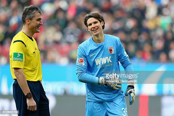 Marwin Hitz of Augsburg smiles with referee Knut Kircher during the Bundesliga match between FC Augsburg and Borussia Moenchengladbach at WWK Arena...