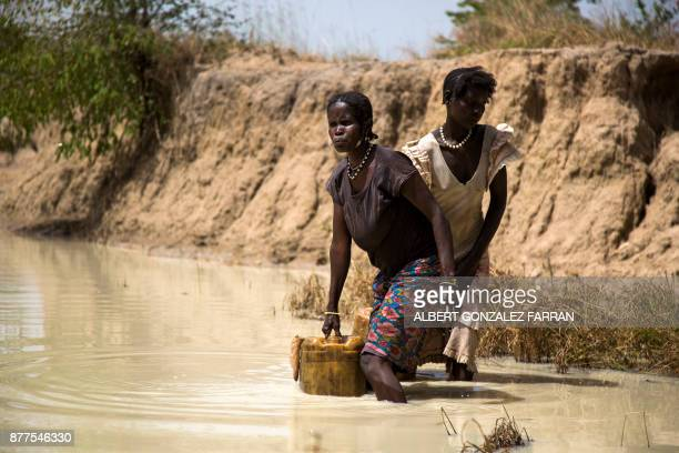 Mary Abong and Alissa Lual two displaced mothers collect water from a road construction site near their Internally Displaced Person camp formed by...