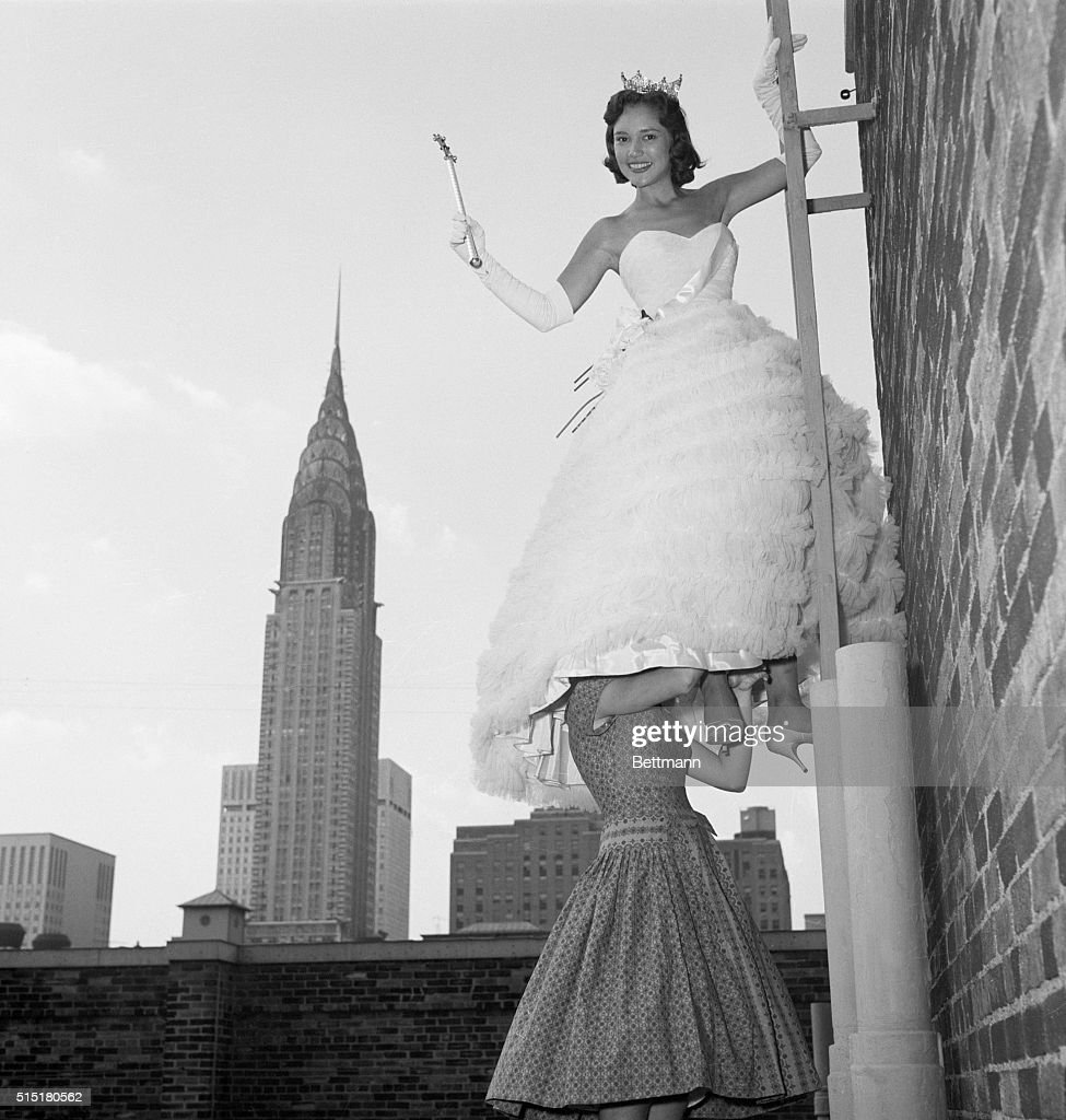 Mary Ann Mobley gets a good look at New York City from a ladder atop the Park Lane Hotel as her twelve year old sister, Sandra, holds on to her legs beneath her pageant dress.