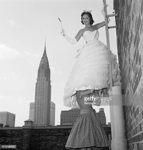Mary Ann Mobley gets a good look at New York City from a ladder atop the Park Lane Hotel as her twelve year old sister Sandra holds on to her legs...