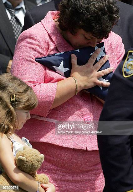 Mary Ann Shortell the widow of NYPD Inspector Michael Shortell hugs her husband's flag as daughter Kerry looks on during funeral services at St...