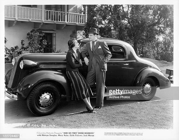 Mary Astor and Melvyn Douglas leaning against a car talking in a scene from the film 'And So They Were Married' 1936