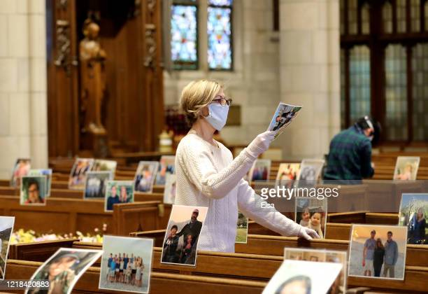 Mary Auer along with other volunteers and church staff affix pictures sent in by parishioners so that they can be there for the live stream of Easter...