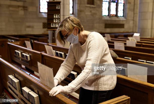 Mary Auer along with other volunteers and church staff affix pictures sent in by parishioners before the live stream of Easter Sunday Mass at Our...