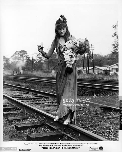 Mary Badham holds a doll as she walks on train track in a scene from the Paramount Pictures movie This Property Is Condemned circa 1966