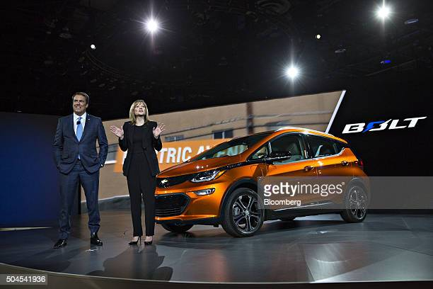 Mary Barra chief executive officer of General Motors Co right speaks next to a 2017 Chevrolet Bolt EV as Mark Reuss executive vice president of...