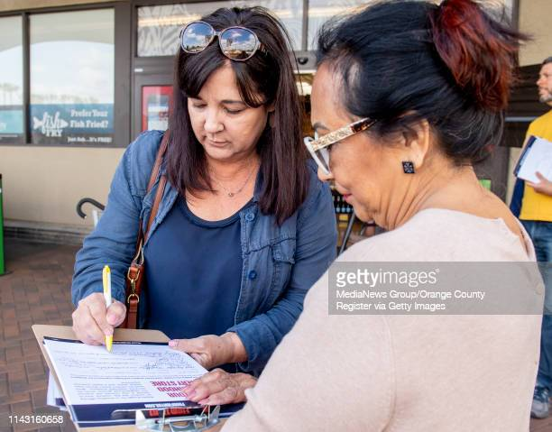 Mary Batson, left, of North Tustin signs a petition in support of grocery workers outside a Ralphs in Tustin on Tuesday, April 16, 2019. UFCW Local...