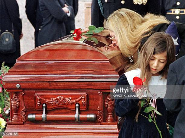 Mary Bono the widow of Sonny Bono kisses his casket as her daughter Chianna holds a rose during burial services at Desert Memorial Cemetery in...