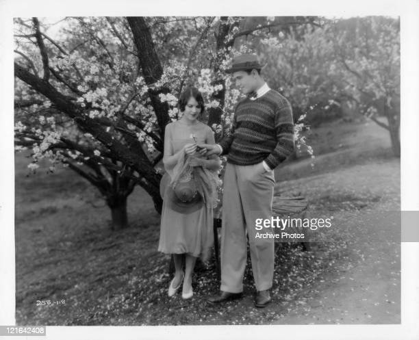 Mary Brian and William Haines standing out among the blossoms in a scene from the film 'Brown Of Howard' 1926