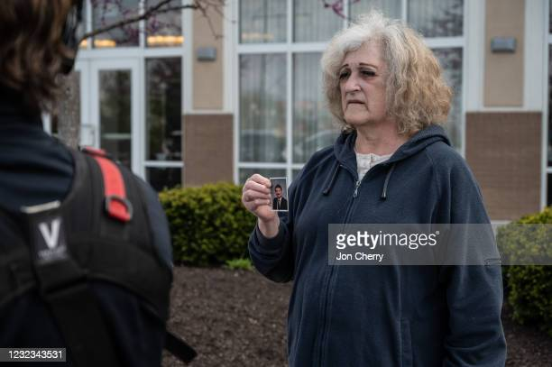 Mary Carol Weisert displays a picture of her husband, John Weisert, near his workplace at a FedEx ground facility on April 16, 2021 in Indianapolis,...