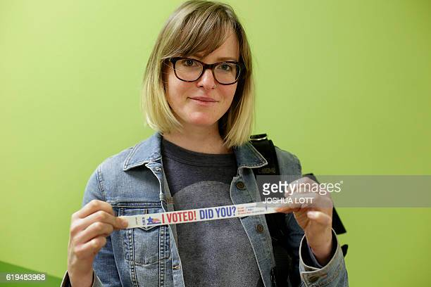 Mary Claire Runchey poses for a portrait with her I Voted Did You risk band after voting early at a polling station inside Truman College on October...
