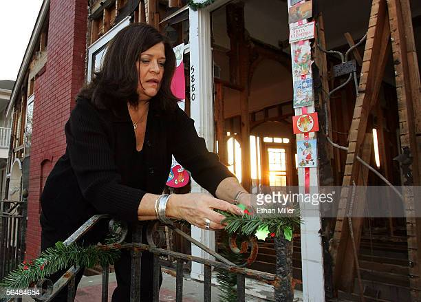 Mary Davis ties holly to a rail at her son Michael's house in the Lakeview District December 23, 2005 in New Orleans, Louisiana. Davis said she...