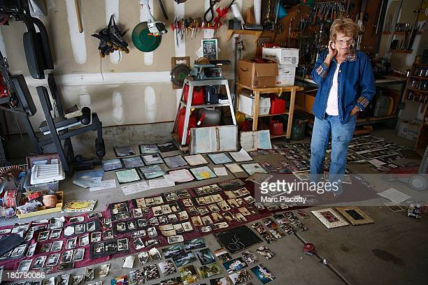 Mary Ellen Briscoe of Longmont Colorado pauses in her garage as she looks over historic family photos trying to dry that were flooded in her basement...