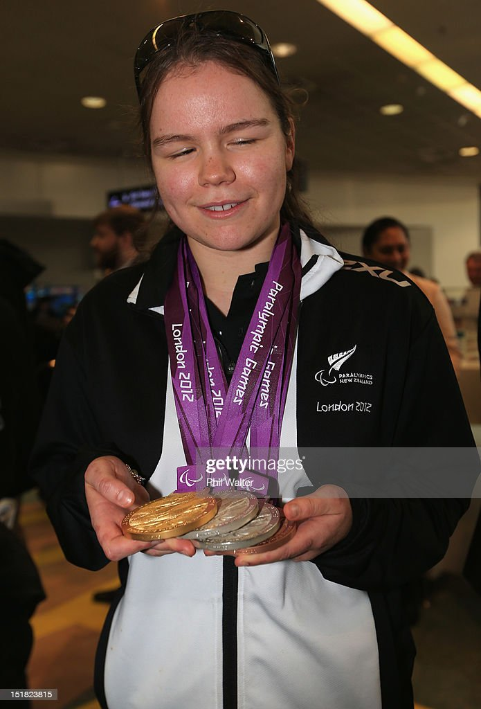 Mary Fisher holds up her medals from the London Paralympics, during the New Zealand Paralympians arrival home at Auckland International Airport on September 12, 2012 in Auckland, New Zealand.