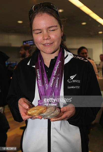 Mary Fisher holds up her medals from the London Paralympics during the New Zealand Paralympians arrival home at Auckland International Airport on...