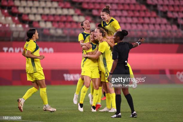 Mary Fowler of Team Australia celebrates with team mates after scoring their side's third goal during the Women's Quarter Final match between Great...