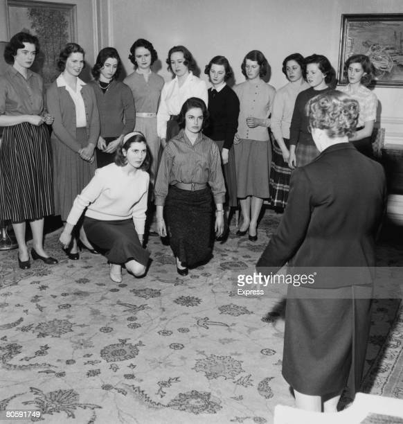 Mary Groves and Juliet Musker are amongst the debutantes learning to curtsey before they are presented to the Queen 2nd March 1958
