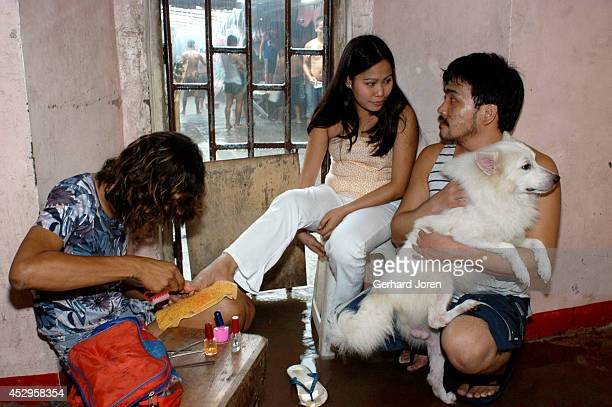 Mary Jane Palima gets a manicure from an inmate while talking to her boyfriend Anthony Chiu in their VIP cell at the Sputnik gang barrack at the...