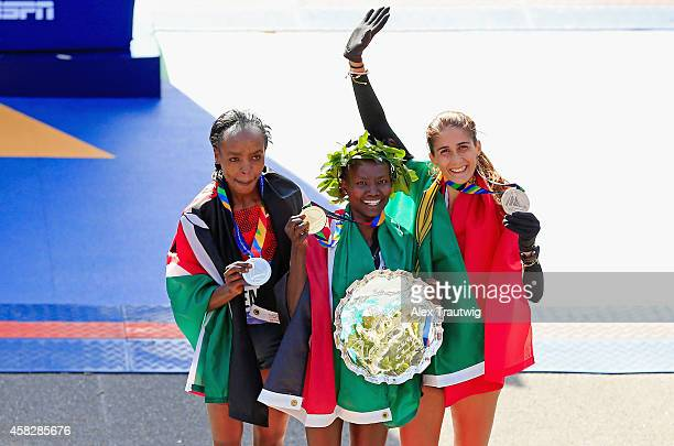 Mary Keitany of Kenya celebrates with the first place trophy alongside second place Jemima Sumgong of Kenya and third place Sara Moreira of Portugal...