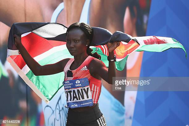 Mary Keitany of Kenya celebrates with the Kenyan flag after finishing first in the Professional Women's Division during the 2016 TCS New York City...