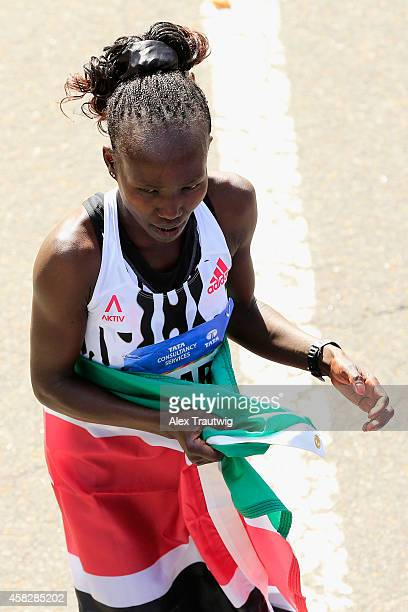 Mary Keitany of Kenya celebrates wrapped in a flag after crossing the finish line to win the Pro Women's division during the 2014 TCS New York City...