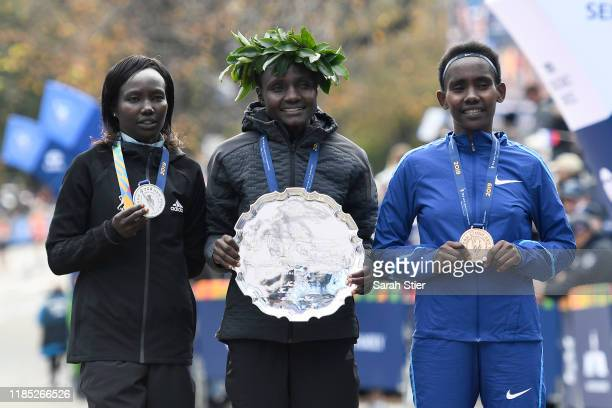 Mary Keitany of Kenya Joyciline Jepkosgei of Kenya and Ruti Aga of Kenya pose with the trophy after taking the top three spots in the Women's...