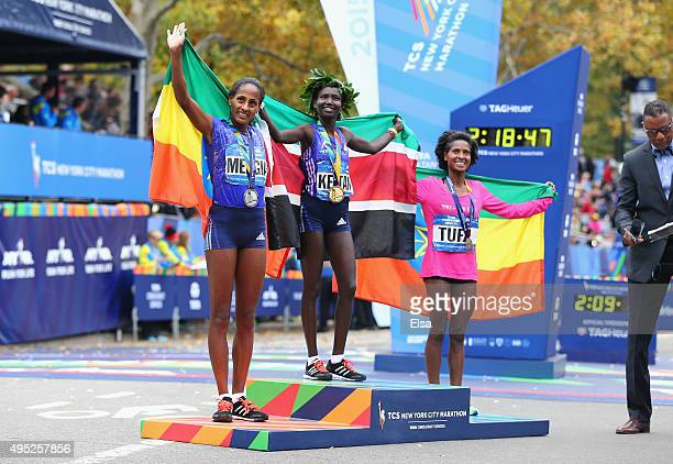 Mary Keitany of Kenya poses alongside second place Aselefech Mergia of Ethiopia and third place Tigist Tufa of Ethiopia during the trophy...
