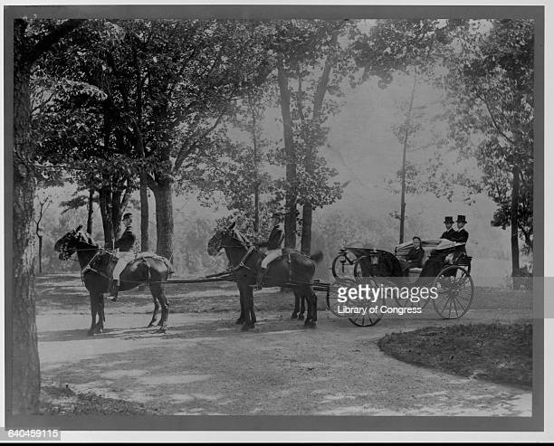 Mary L McLean on a horsedrawn carriage accompanied by liveried footmen and uniformed outriders Washington DC ca 1900s