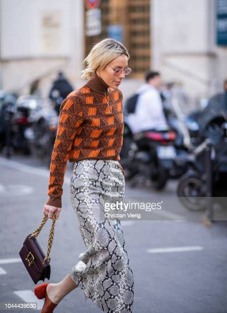 Mary Lawless Lee wearing snake print skirt with slit zipped sweater brown bag is seen outside Sacai during Paris Fashion Week Womenswear...