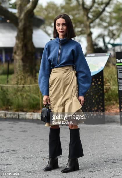 Mary Leest is seen wearing a blue zippered sweatshirt beige skirt and black boots outside the Carolina Herrera show during New York Fashion Week...