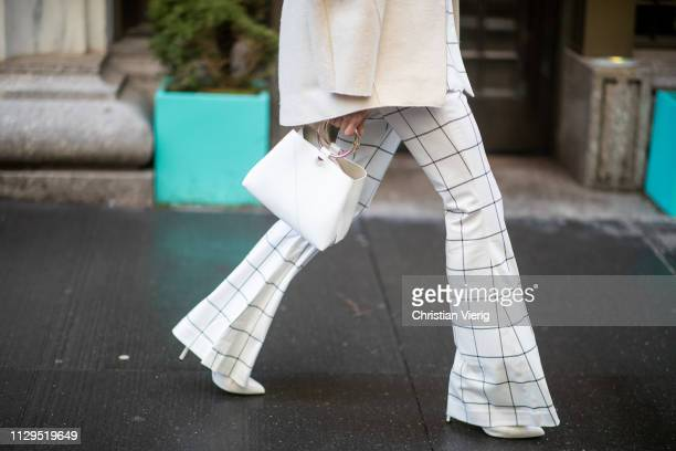 Mary Leest is seen wearing white plaid flared pants white bag outside Michael Kors during New York Fashion Week Autumn Winter 2019 on February 13...