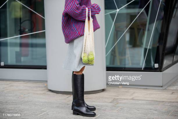 Mary Leest seen wearing knit skirt with slit net bag with apples black boots outside the Sportmax show during Milan Fashion Week Spring/Summer 2020...