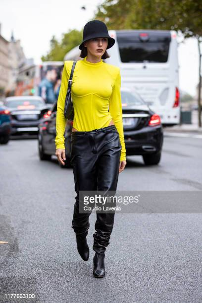 Mary Leest wearing a yellow top black leather pants black hat and black boots is seen outside the Unravel show during Paris Fashion Week Womenswear...