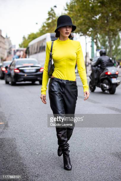 Mary Leest, wearing a yellow top, black leather pants, black hat and black boots, is seen outside the Unravel show during Paris Fashion Week -...