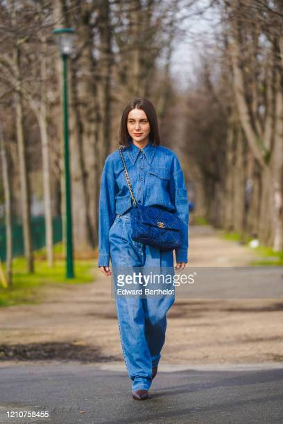 Mary Leest wears a blue denim shirt, a blue large quilted Chanel bag, blue denim jeans, pointy leather brown shoes, outside Chanel, during Paris...