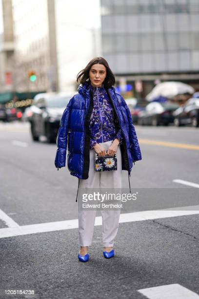 Mary Leest wears a blue shiny puffer coat, a blue floral print jacket, a floral print rigid bag, gray pants, blue pointy shoes, outside Tory Burch,...