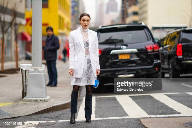 Mary Leest wears a white jacket with floral embroidery, a white lace mesh ruffled dress, a blue bag, black tights, black leather shoes, during New...