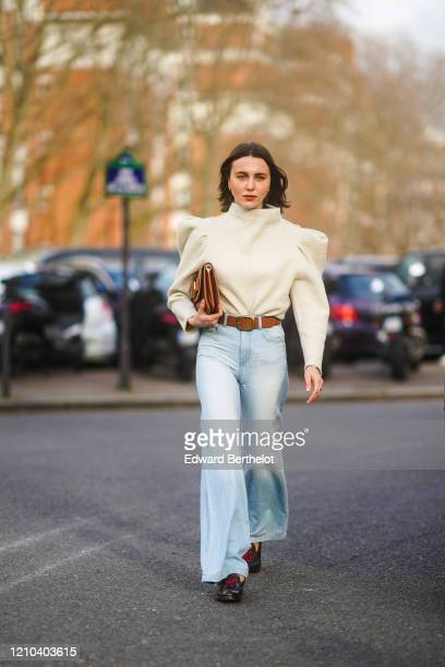 Mary Leest wears a white top with shoulder pads, a brown leather clutch, a brown leather belt, pale blue denim flared pants, shoes, outside Lacoste,...