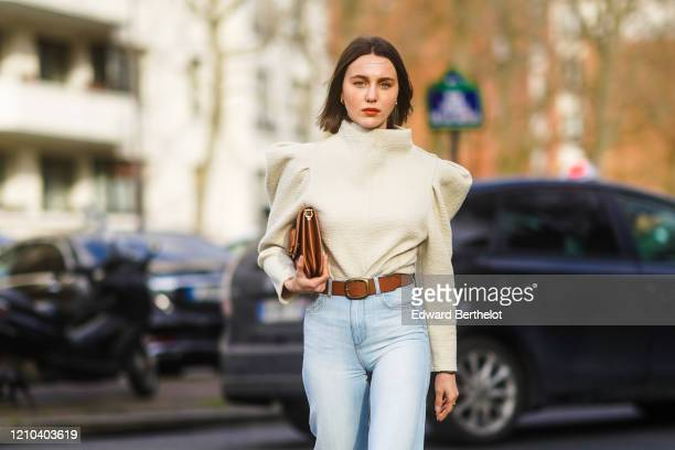 Mary Leest wears a white top with shoulder pads a brown leather clutch a brown leather belt outside Lacoste during Paris Fashion Week Womenswear...