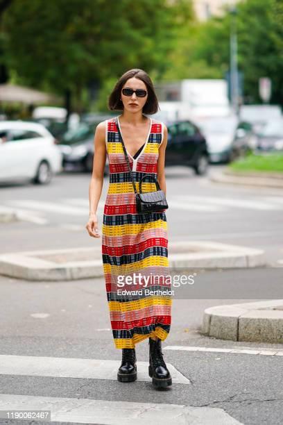 Mary Leest wears sunglasses a black crocodile pattern crossbody bag a red black pink and yellow stripes long dress with a plunging neckline black...