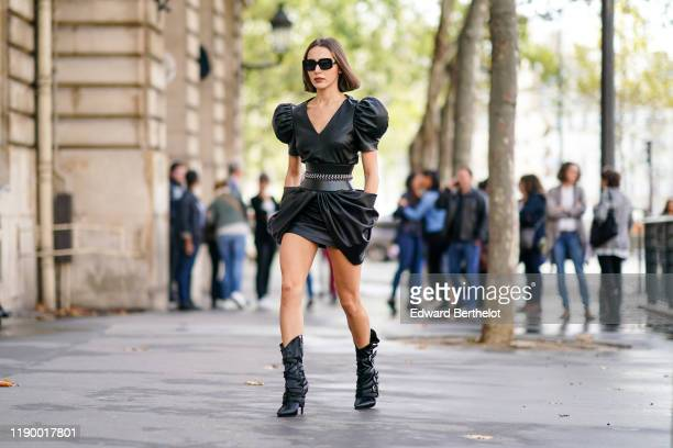 Mary Leest wears sunglasses a black leather dress with puff shoulder pads and ruffles black boots outside Redemption during Paris Fashion Week...